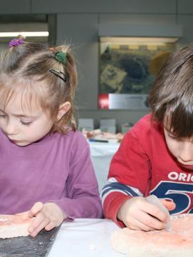 Photographie de deux enfants participant à une animation consacrée à la gravure préhistorique