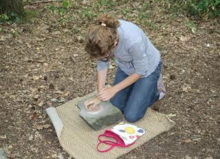 Un enfant s'essaye à la mouture du grain à l'aide d'une meule et d'un broyeur en pierre