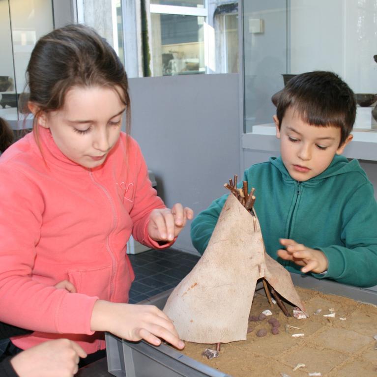 Animation pédagogique consacrée à l'habitat préhistorique. Ici, construction d'une maquette de tente en bois et peau d'animal