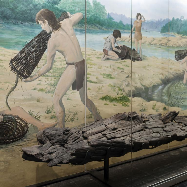 Salle 5 du musée. Vitrine présentant une pirogue préhistorique au pied d'une peinture murale, signée Gilles Tosello,illustrant la vie quotidienne au Mésolithique