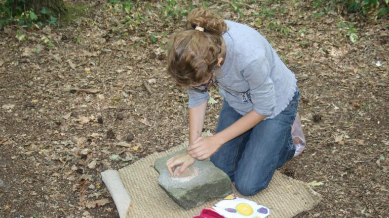 Animation pédagogique au cours de laquelle les enfants écrasent du blé à l'aide d'une meule et d'un broyeur en pierre