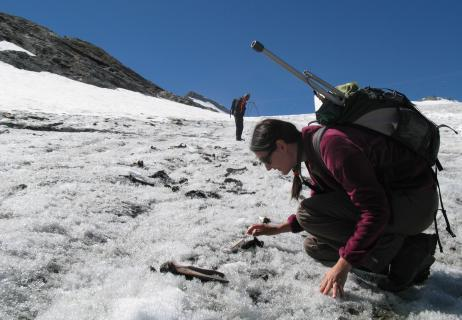Photo d'une archéologue réalisant un prospection archéologique sur un glacier alpin